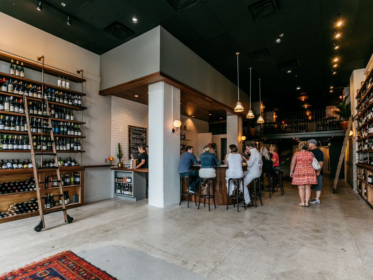 A large, high-ceilinged wine bar with people gathering around the bar