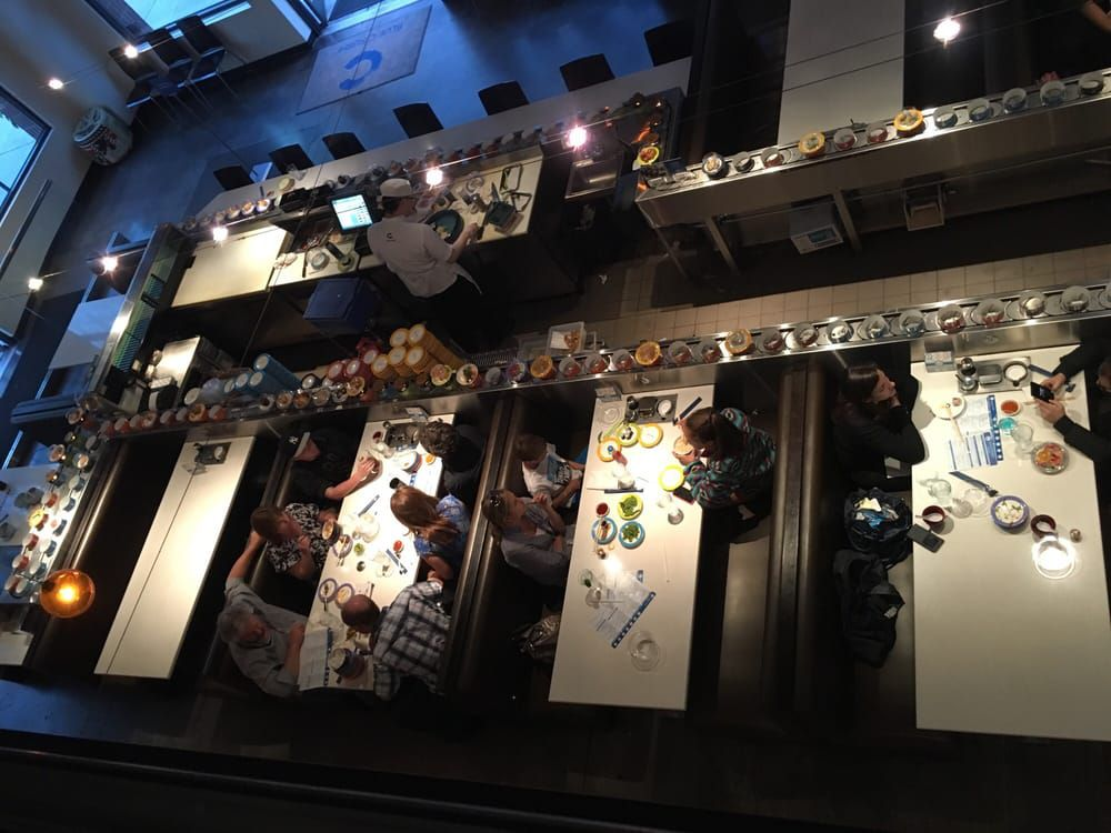 A bird's eye view from the second level of the a Blue C restaurant, showing a conveyor belt transporting plates and a group of diners in booths.