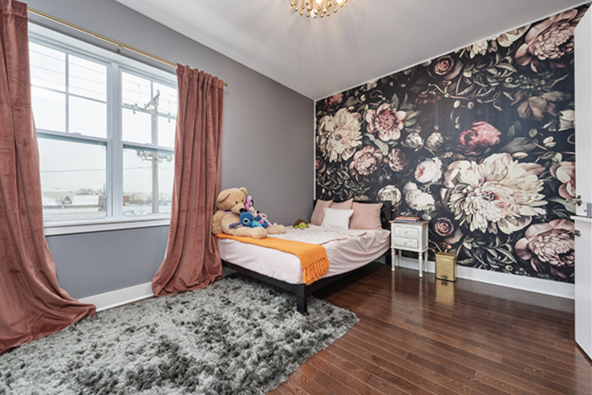 Another bedroom with pink curtains, moody floral wallpaper, and a bed with pink sheets.