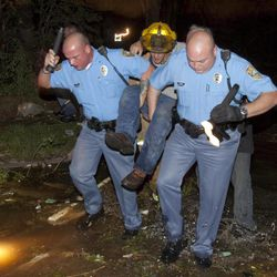 """Sheriff's deputies carry out an injured man from a south Wichita neighborhood after a tornado caused massive destruction in Wichita, Kansas on Saturday night April 14, 2012. Tornadoes were spotted across the Midwest and Plains on Saturday as an outbreak of unusually strong weather seized the region, and forecasters sternly warned that """"life-threatening"""" weather could intensify overnight."""