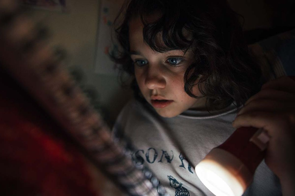 A young girl, Wendy, reads with a flashlight under her covers.