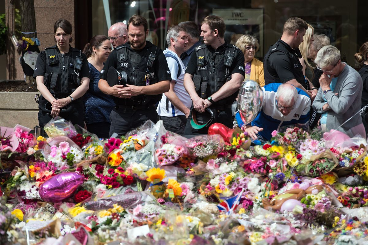 Police officers join members of the public to view the flowers and messages left in honor of the victims of the recent terrorist attack in Manchester.