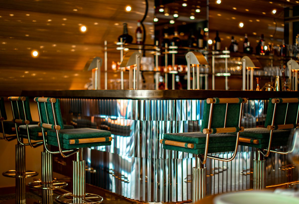 A shiny metallic bar with unique green felt bar stools, industrial table lamps at each place, and a gold back bar marked by dots of light