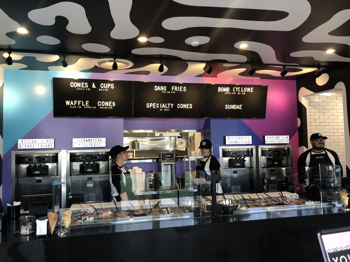 A photo of three employees standing at the counter at Dang with the four soft serve machines built into the wall behind them and a counter containing over 30 toppings visible in front of them