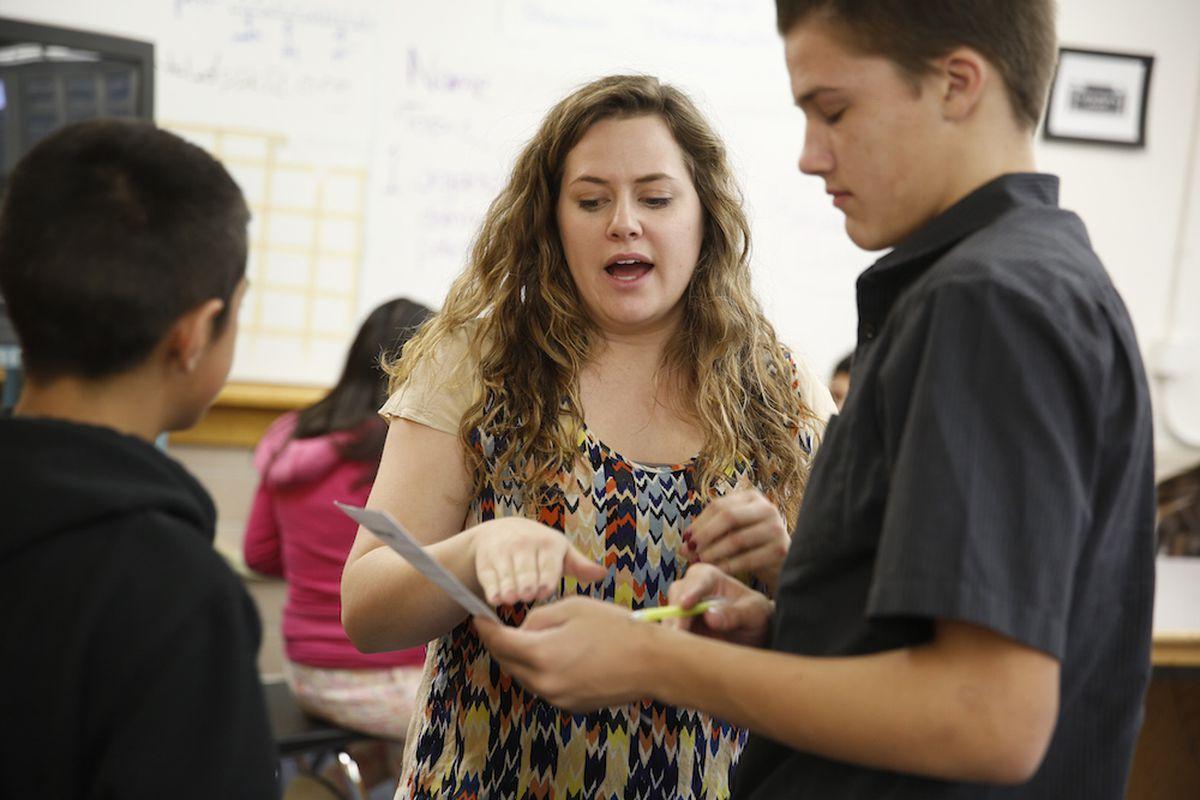 Manual High School teacher Olivia Jones reviews classwork with a student in 2013.