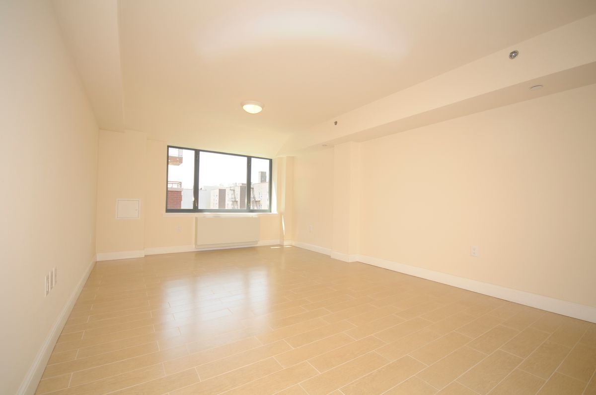 A living area with hardwood floors, beige walls, and a large window.