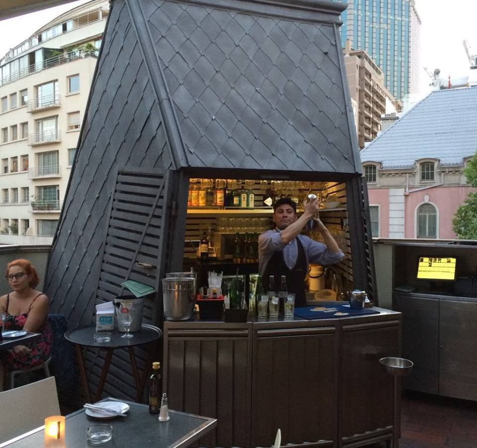 A bartender shakes a cocktail high in the air in a one-person kiosk bar, paneled and built in an odd shape, on an outdoor terrace beside tables full of customers