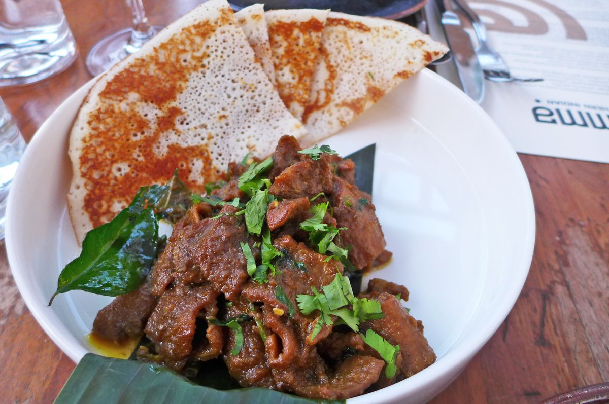 A gnarly pile of goat intestines on a banana leaf with a quartered flatbread at the top of the picture.