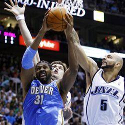 Carlos Boozer (5) of the Utah Jazz and teammate Kyrylo Fesenko (44) of the Utah Jazz defend Nene (31) of the Denver Nuggets.