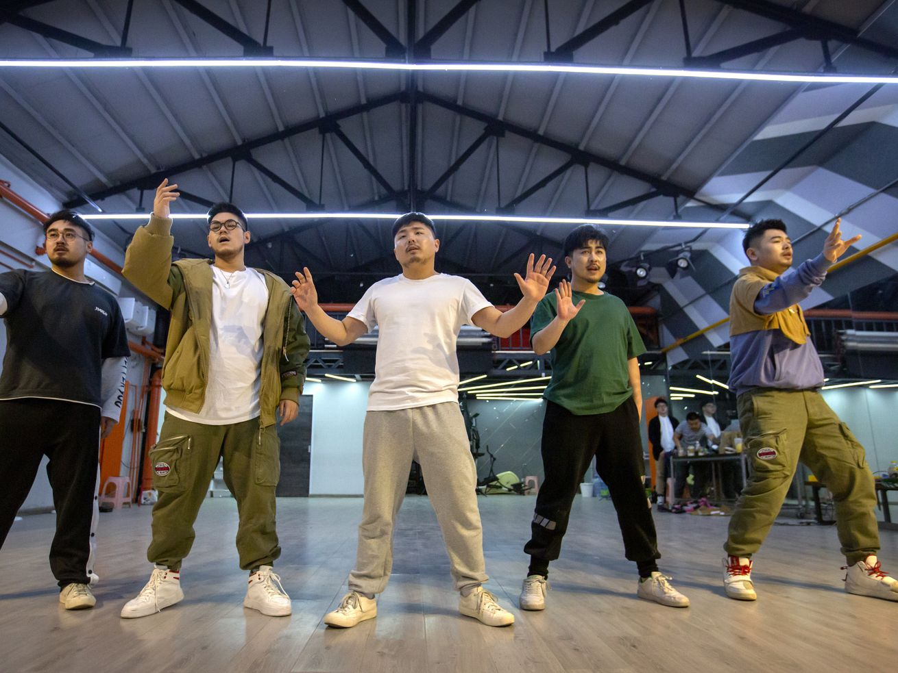 """Members of the Chinese music group Produce Pandas — DING (from left), Husky, Otter, Cass and Mr. 17 — strike a pose while practicing dance choreography during rehearsals in Beijing earlier this month. The groups proudly call themselves """"the first plus-sized boy band in China."""""""