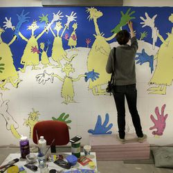"""In this May 4, 2017 photo Cortney Thibodeau, a senior at University of Massachusetts at Amherst, paints a mural based on artwork from the Dr. Seuss book """"Oh, The Thinks You Can Think!"""" at The Amazing World of Dr. Seuss Museum, in Springfield, Mass. The museum devoted to Dr. Seuss, which opened on June 3 in his hometown, features interactive exhibits, a collection of personal belongings and explains how the childhood experiences of the man, whose real name is Theodor Geisel, shaped his work."""