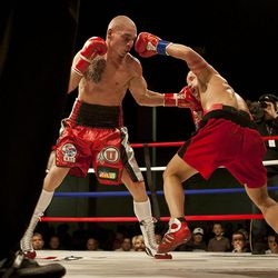 """Chris """"KidKayo"""" Fernandez, left, lands a left jab against Allen Litzau during their boxing match at the South Towne Expo Center. Fernandez won the bout after four rounds, Saturday, Dec. 15, 2012."""
