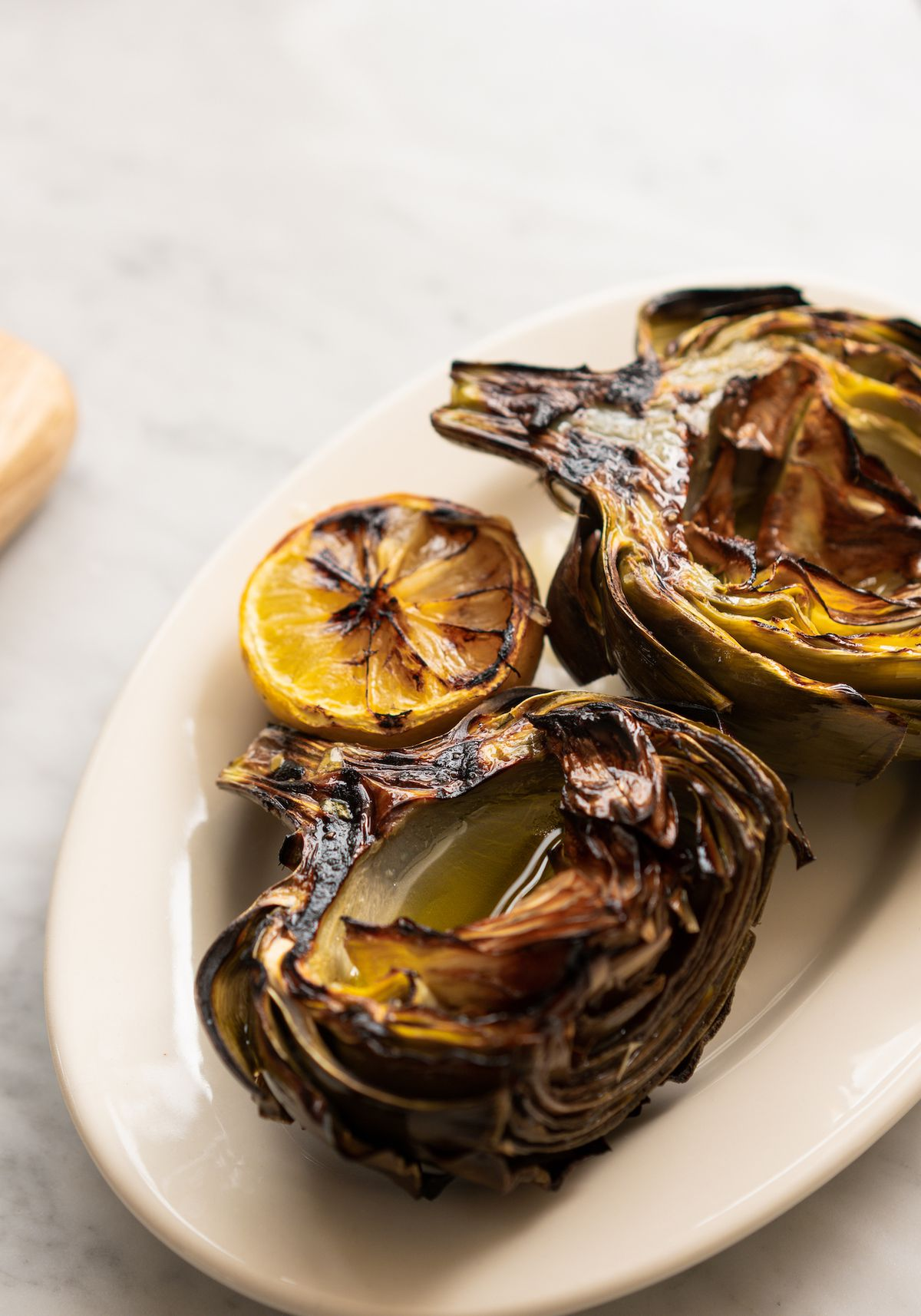 An oval plate of grilled artichokes with lemon on the side.