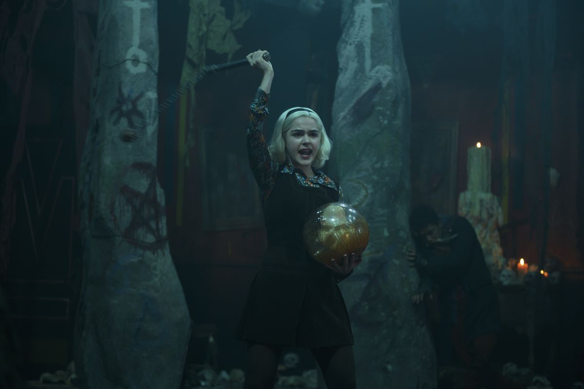 Sabrina stands in a cavelike space surrounded by graffitied pentacles and waves a flail over her head while holding a golden globe in Netflix's Chilling Adventures of Sabrina.