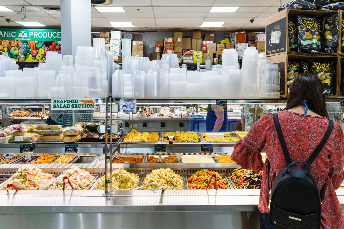 """A woman stands behind a hot buffet, filled with colorful salads; a sign reads """"seafood salad section."""""""