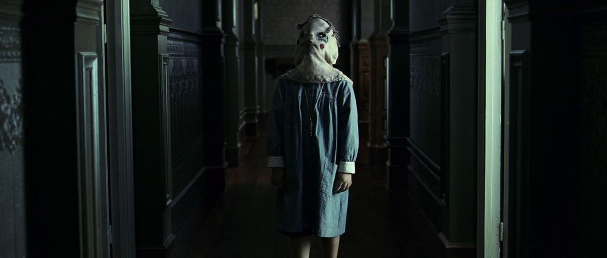 An ominous looking child wearing a sack over their head in The Orphanage.