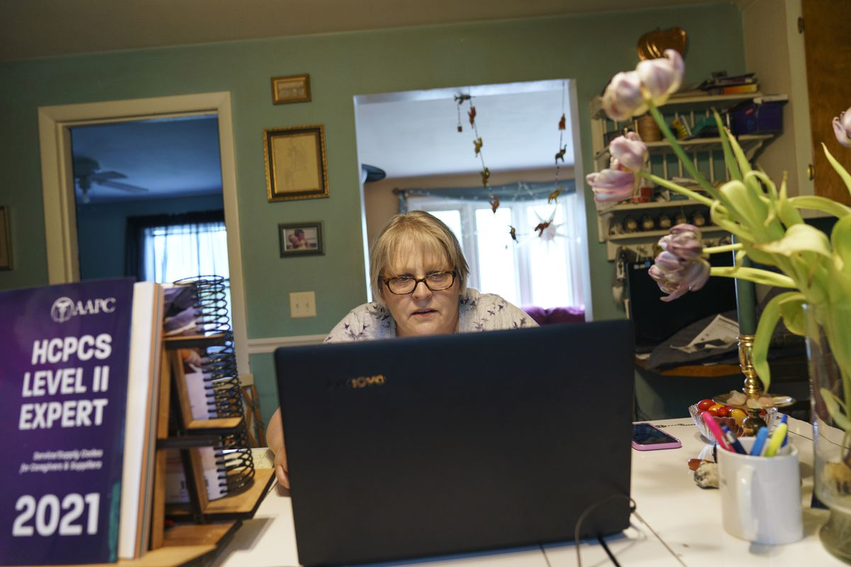 Ellen Booth, 57, studies at her kitchen table to become a certified medical coder, in Coventry, R.I., Monday, May 17, 2021.