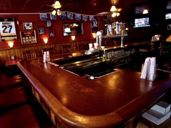 An empty barroom, with a wooden horseshoe bar, Boston sports pennants, and a televisions on the wall
