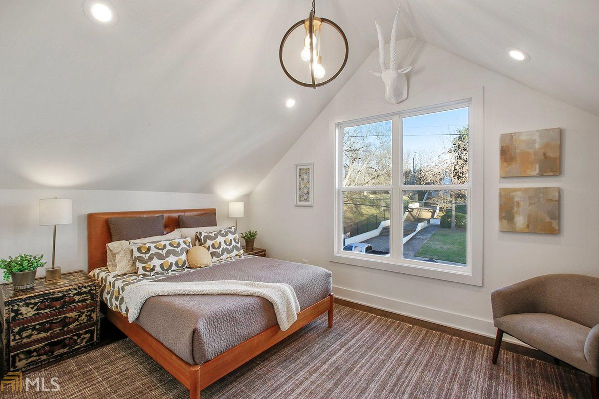Large room with vaulted ceiling, bed, nightstands with lamps and chair.