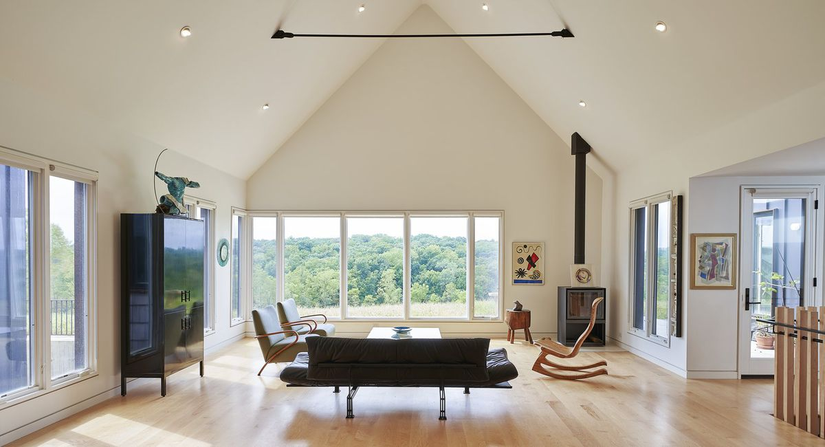 Living room featuring angled roof and large windows.