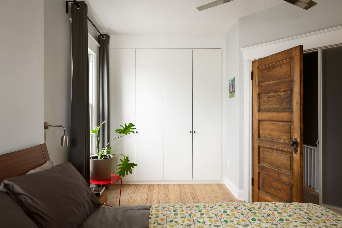 The bedroom has a patterned bed spread, wooden door, and white walls.