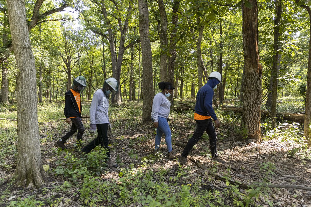 Crew members walk back to the shelter for a break after clearing brush. The county program is educational and assures much-needed maintenance is done at the forest preserves.