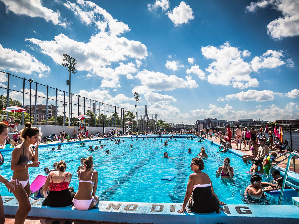 A large outdoor swimming pool with many people.