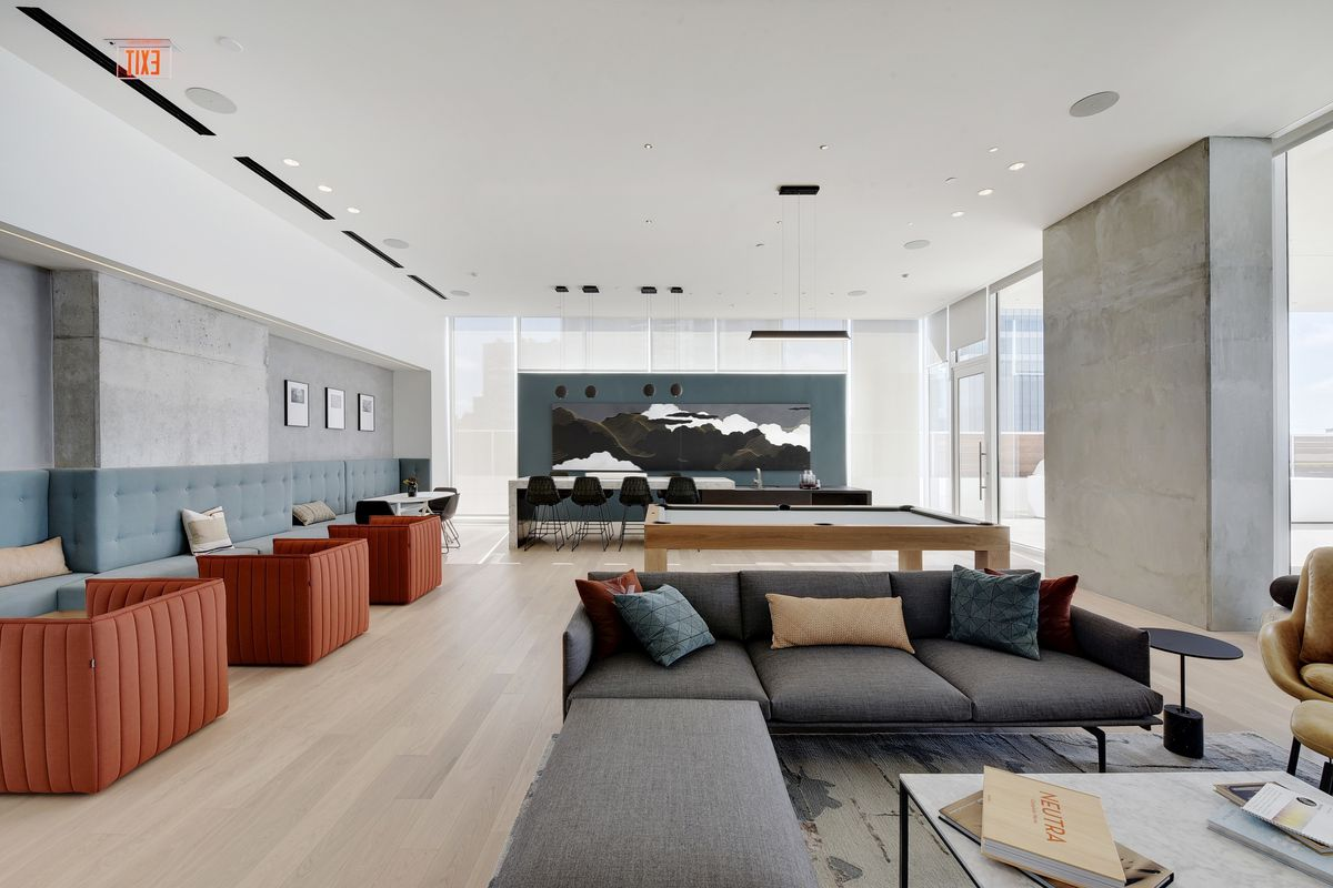 Large room with concrete and large window walls, a light wood floor, a pool table, chairs, couches, and coffee tables arranged in groups.