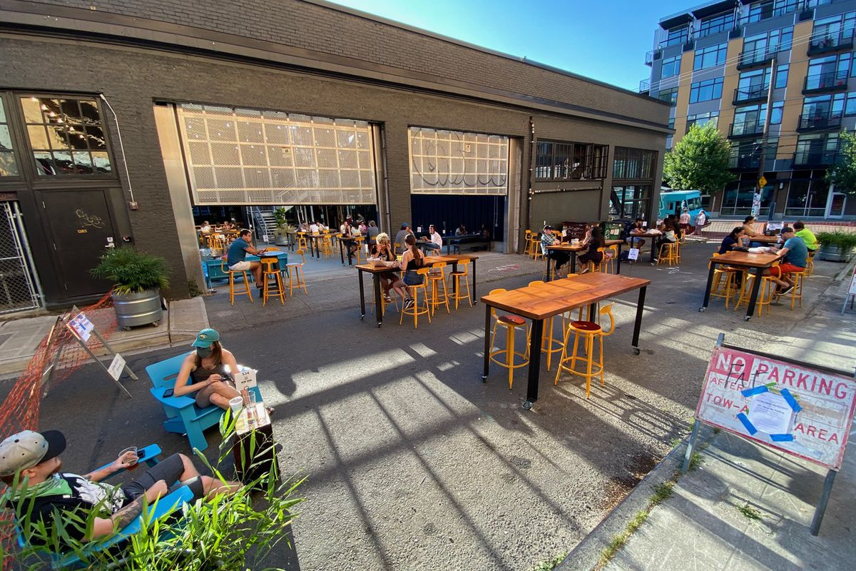 On a sunny day, several tables are set up outside Optimism Brewing on Broadway Court, with masked patrons sitting down