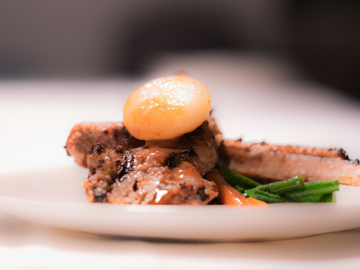 Meat on the bone with an egg yolk perched on top.