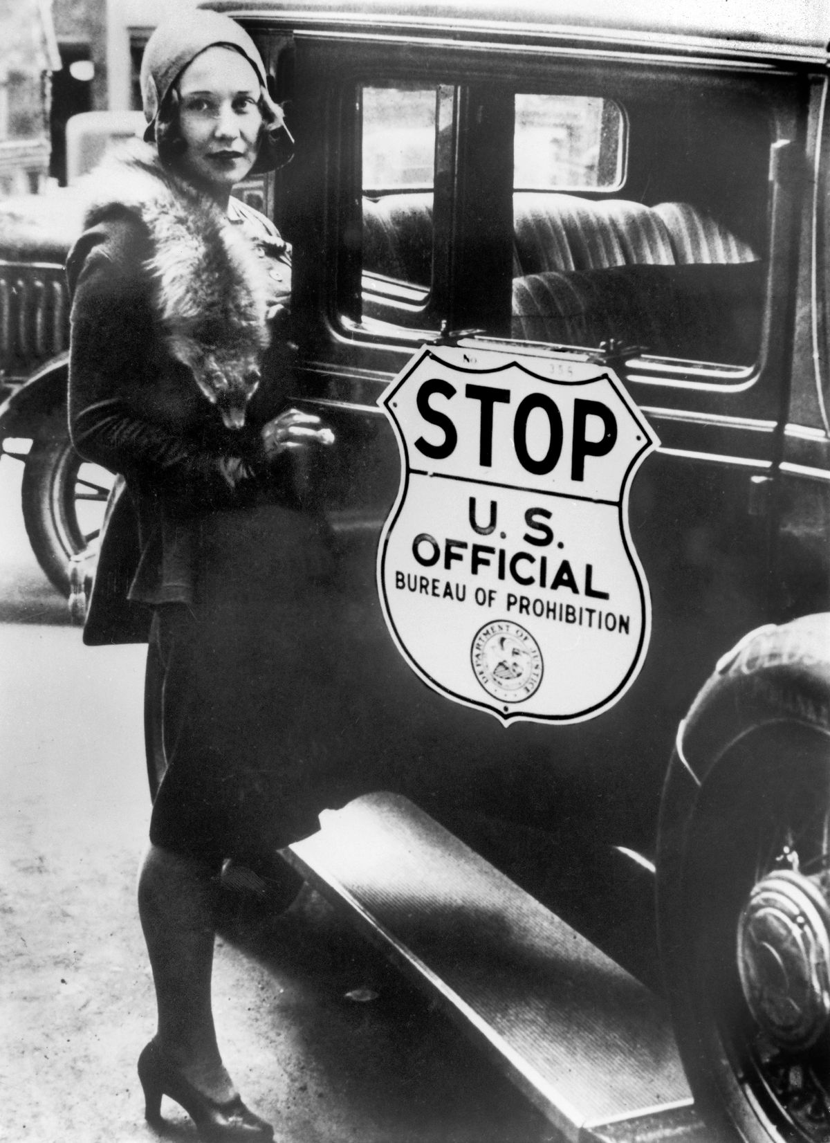 A woman gets into a US Bureau of Prohibition car in 1930.
