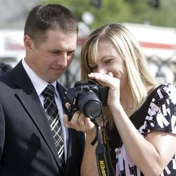 Jason and Jeanna Burnett look at some of their photos as they walk around the temple following the first dedicatory session Sunday, Sept. 23, 2012.