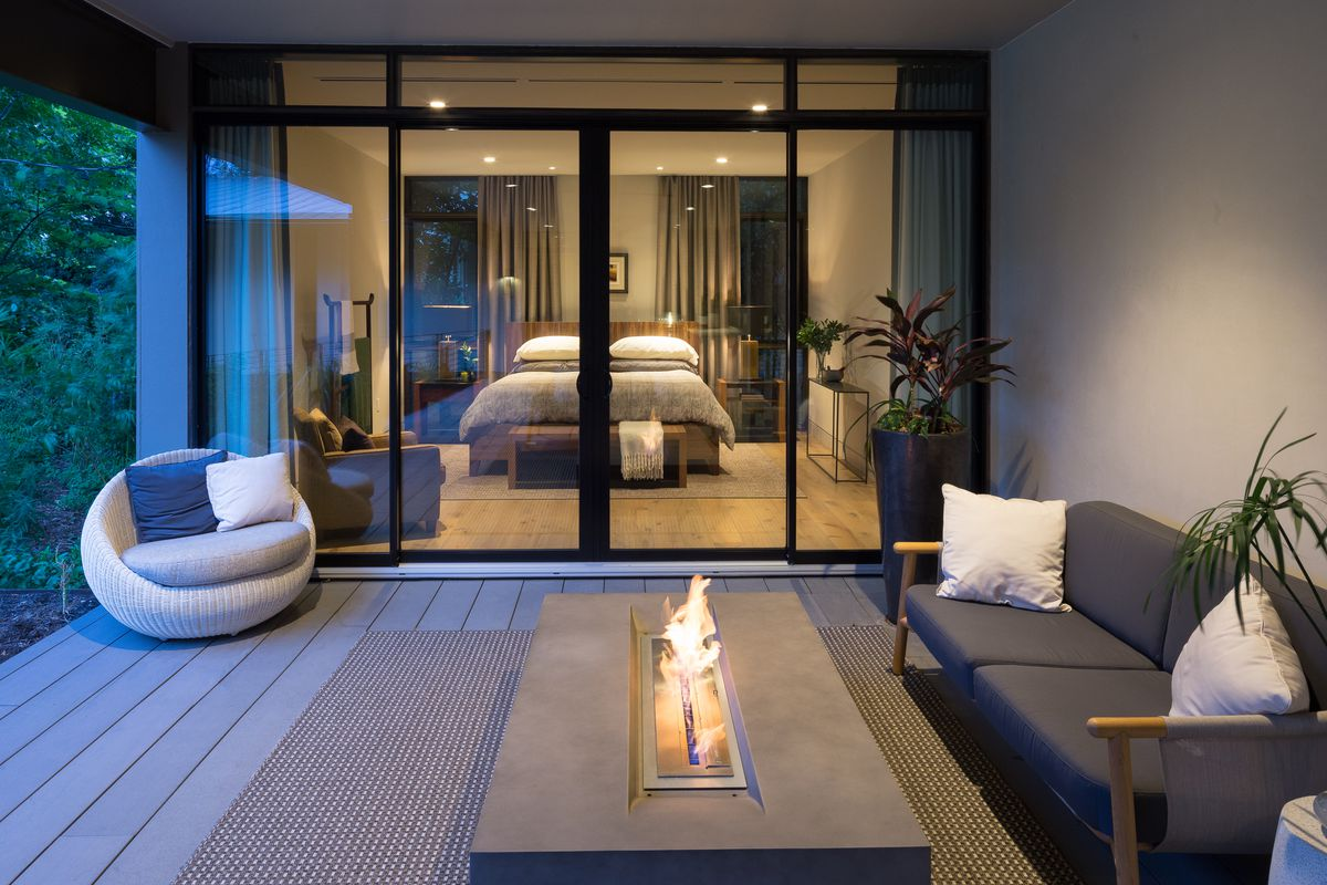 Contemporary porch with sliding glass doors/windows looking into bedroom, couch, mod chair, modern firepit