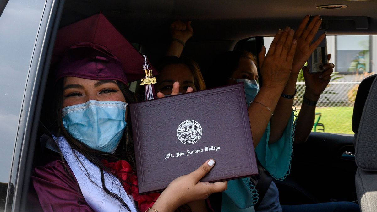 A person wearing a graduation gown and mortar board and facemask sits in the back seat of a car and holds up a diploma.