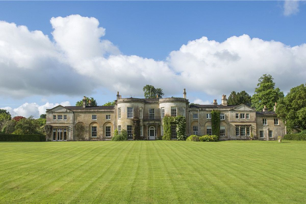 Grand country estate with large manicured lawn in front.