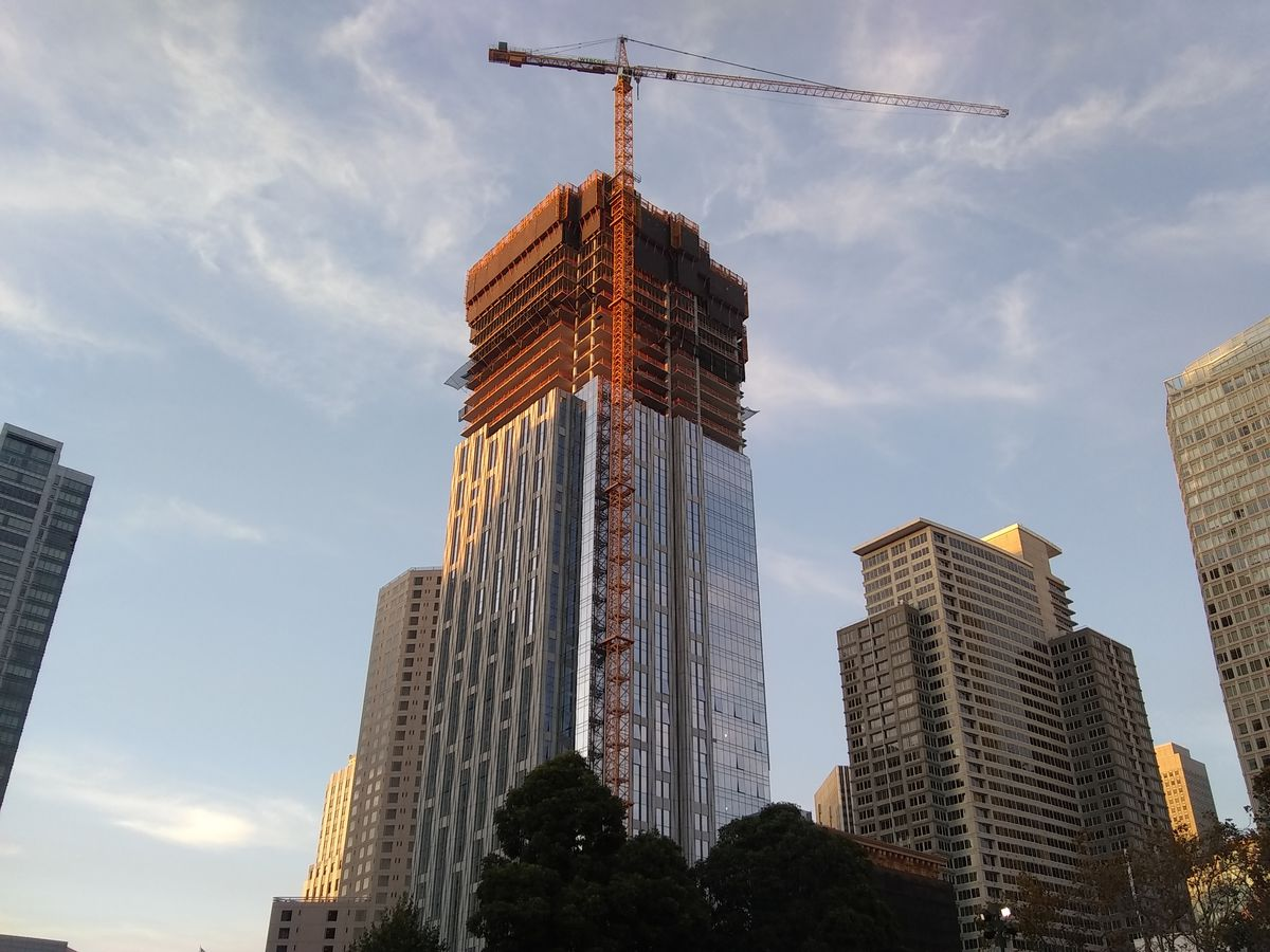 A construction crane perched on top of a partially built skyscraper, with glass installed on the bottom two-thirds of the facade.