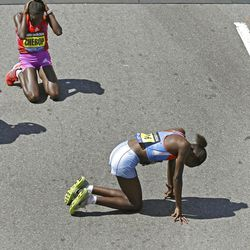 Sharon Cherop, of Kenya, top, reacts after she edged out compatriot Jemima Jelagat Sumgong, bottom, after breaking the tape to win the  women's division of the 116th Boston Marathon in Boston, Monday, April 16, 2012. (AP Photo/Charles Krupa)