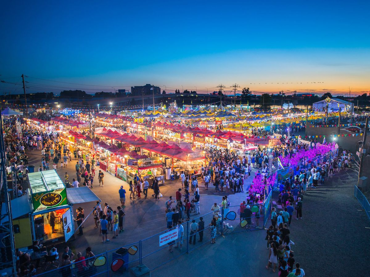 An aerial shot of stalls and tents of a night market at dusk, with crowds of diners lining up to enter and browsing the stands, a large stage at the end of the market to one side, and the Richmond cityscape off to the other