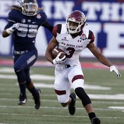 New Mexico State running back Larry Rose III (3) runs away from Utah State linebacker Maika Magalei in the first half of the Arizona Bowl NCAA college football game Friday, Dec. 29, 2017, in Tucson, Ariz. (AP Photo/Rick Scuteri)