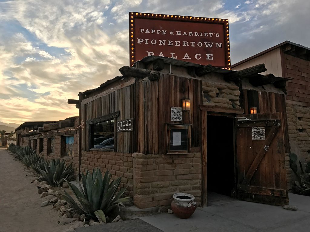 The exterior of a wood and brick house in a desert. There is a sign above the house that reads: Pappy and Harriets Pioneertown Palace.