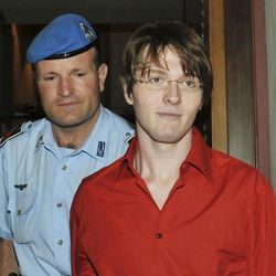 FILE - In this June 26, 2009 file photo, murder suspect Raffaele Sollecito is escorted by a penitentiary police officer as he arrives for a hearing in the Meredith Kercher murder trial, in Perugia, Italy. Sollecito, whose budding love affair with American exchange student Amanda Knox helped land him in an Italian prison for four years, maintains the couple's innocence in a new book but acknowledges that their sometimes bizarre behavior after her roommate's killing gave police reason for suspicion.