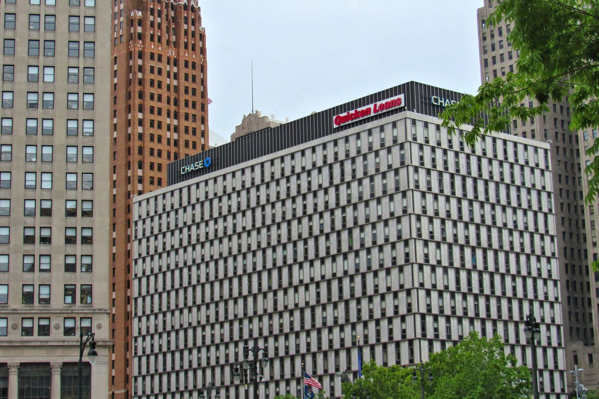 """A multi-story rectangular building with alternating windows white cladding. The top of the building has the words """"Quicken Loans."""""""