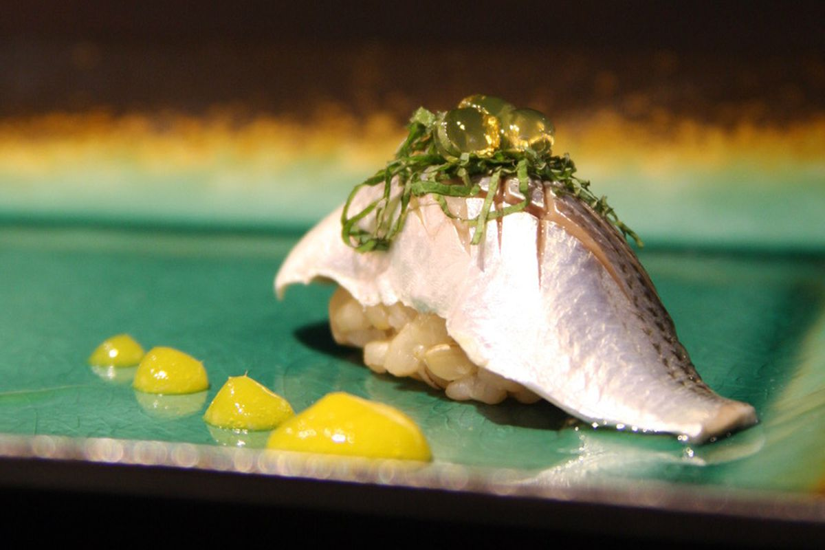 A single piece of sushi sits on a turquoise plate with dots of a yellow sauce to its side