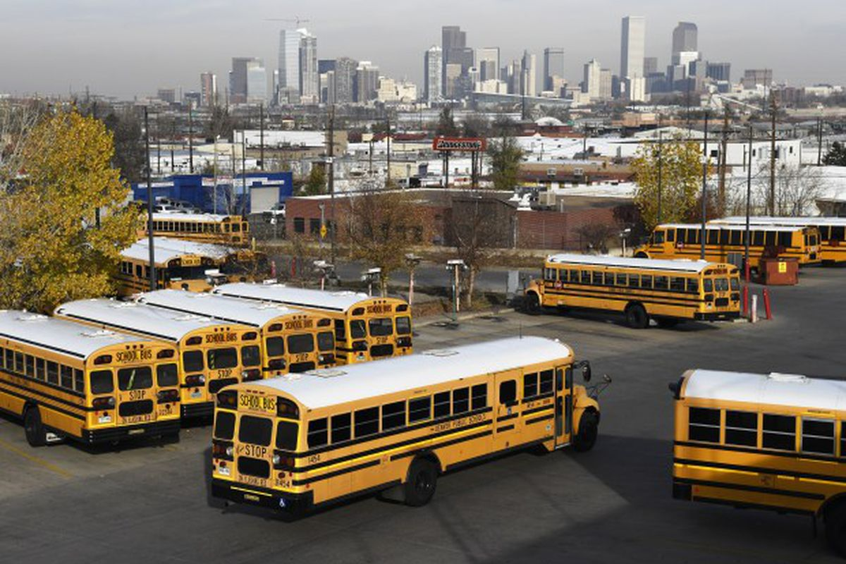 Yellow school buses head out past other parked buses in a terminal lot.