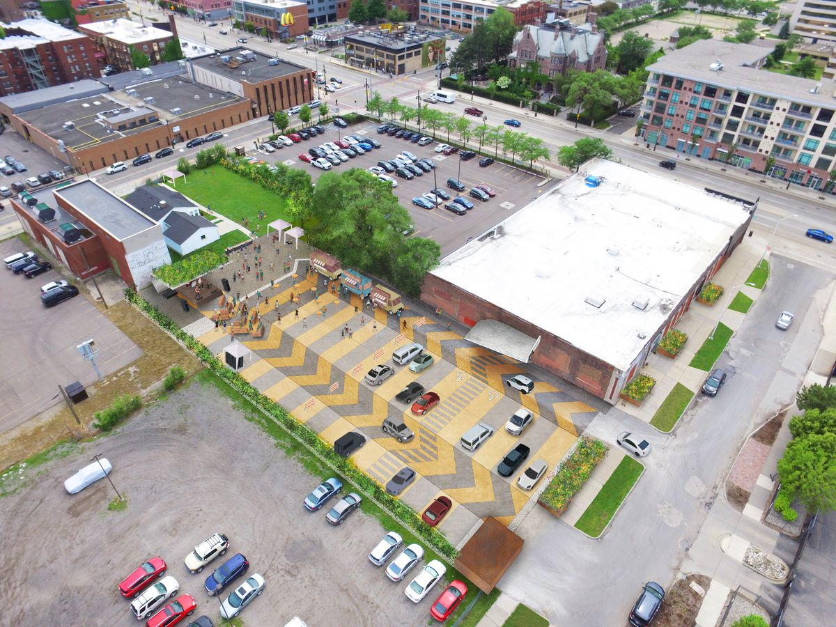 Overhead view of a parking lot with yellow and gray strikes indicating parking and wayfinding. There's a low, rectangular building with a white roof next door.