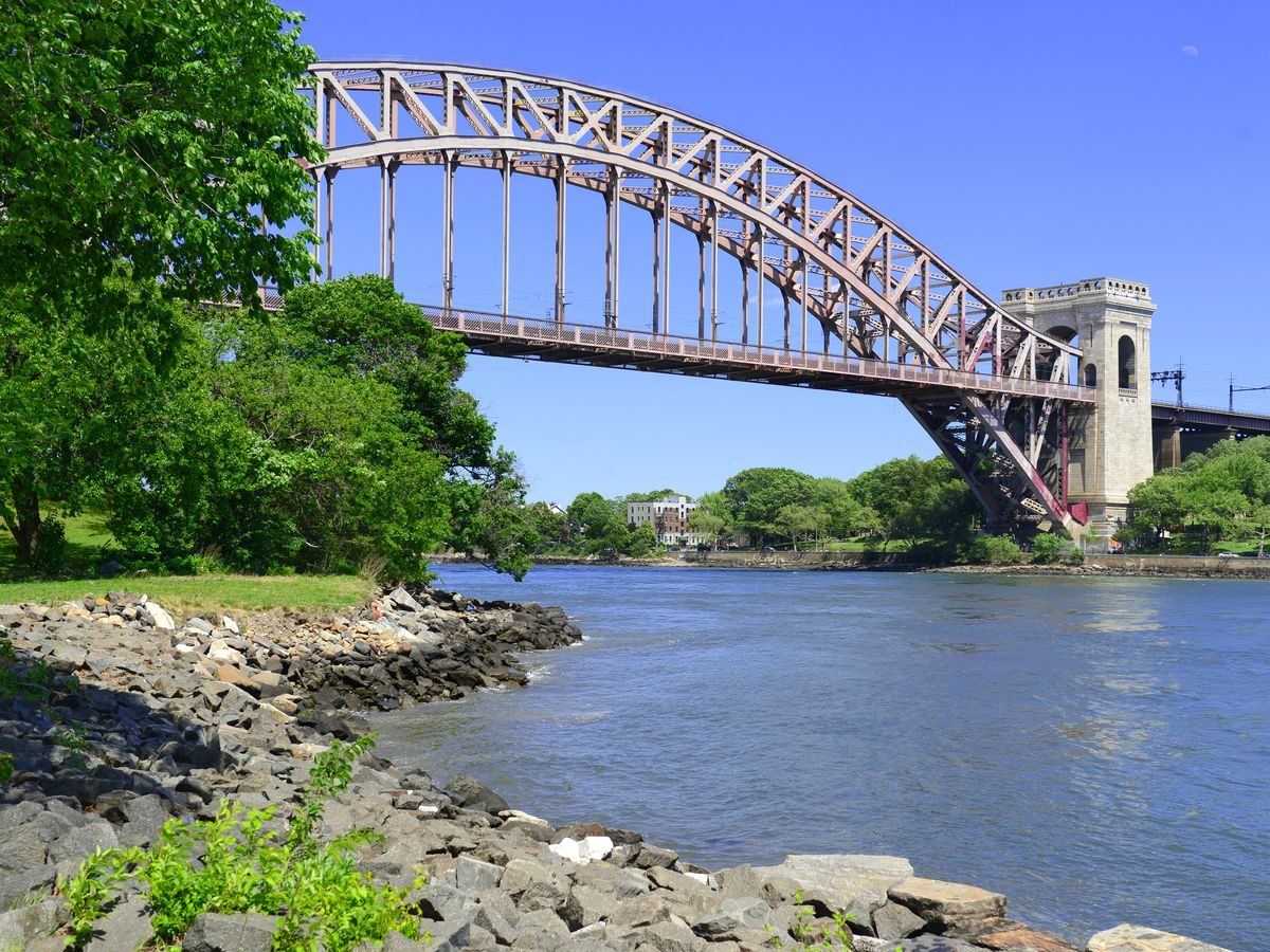 A park. There is a large body of water with rocks to the side of it. In the distance is a bridge spanning the body of water and trees.
