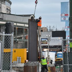 Cable being removed from the steel beam that is being lowered on the Clark Street side of the triangle lot