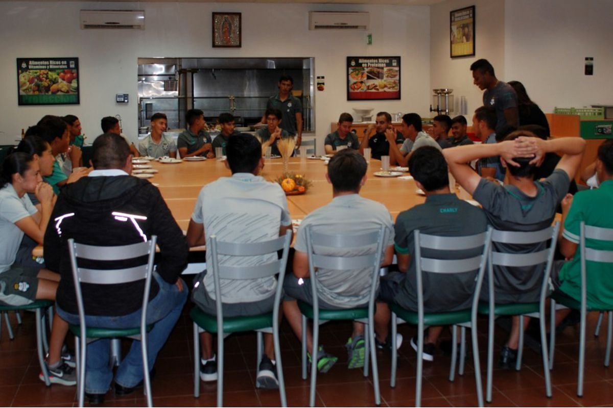 Players and staff of Club Santos Laguna gather around for Thanksgiving dinner.