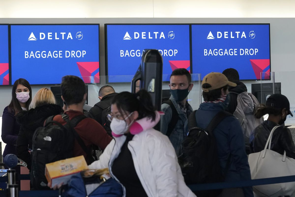Travelers wait in line at a Delta Air Lines gate at San Francisco International Airport during the coronavirus pandemic in San Francisco, Tuesday, Dec. 22, 2020.