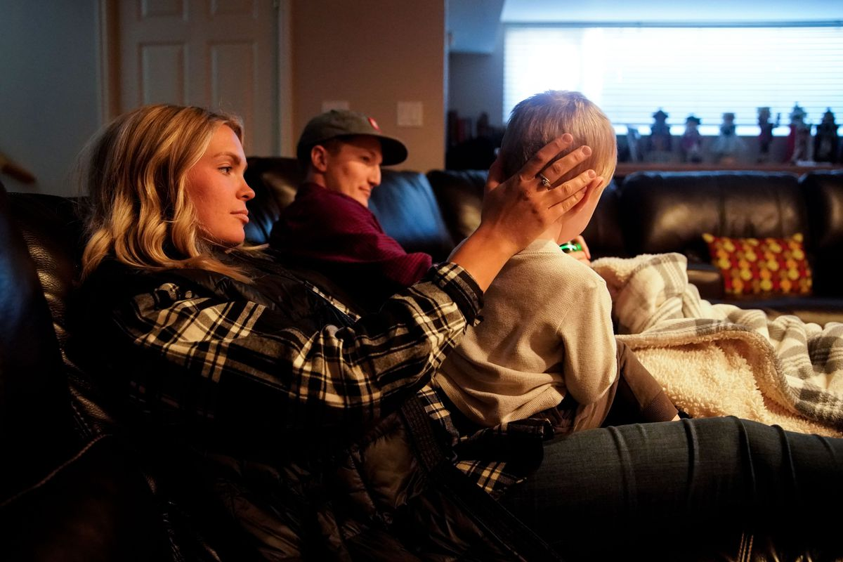Haley Jeppson pats son Sammy, 2, on the head as husband Brookston sits next to her at Haley Jeppson's parents' home in Salt Lake City on Sunday, Oct. 3, 2021.